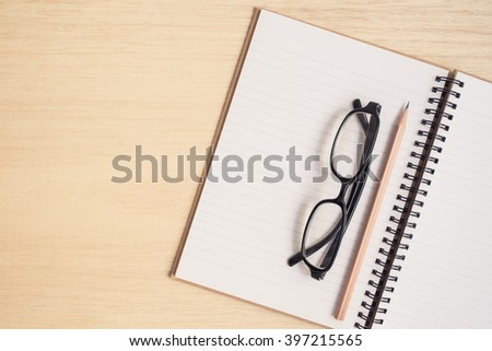 Top view of office desk table with spiral notebook, pencil, and black glasses on wood table - Vintage tone - stock photo