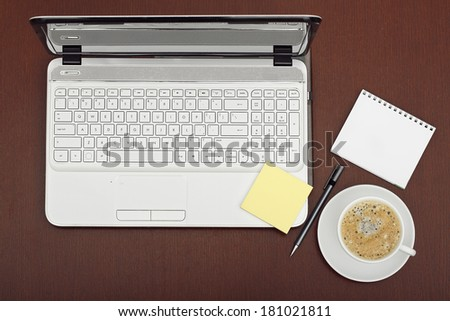 top view of office desk with laptop and coffee - stock photo
