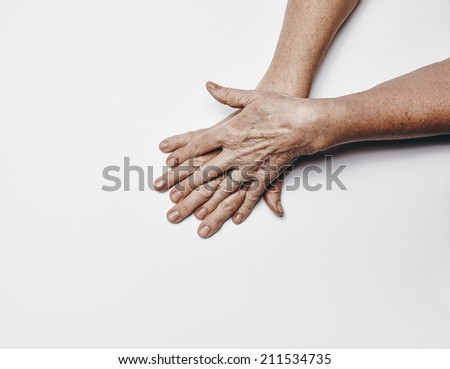 Top view of old female hands with fingers crossing. Senior woman hands isolated on white background  with copy space. - stock photo