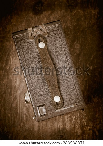 Top view of old retro film camera lying on wooden table. Photographic nostalgia with old-fashioned photo equipment. Conceptual image of old technology with a vintage look.