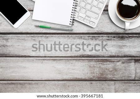 Top view of old wood office table with supplies. Top view with copy space. Modern working life concept. - stock photo