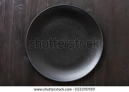 top view of one black plate on dark brown table