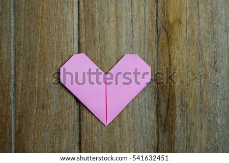Top view of one pink heart  paper on wooden background idea, selective focus, valentine day.