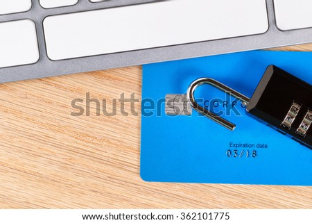 Top view of open combination lock on top of credit card next to partial computer keyboard on oak wood desktop. Keyboard is nonfunctional generic.  - stock photo