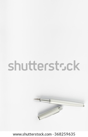 Top view of open ink pen lying on blank sheet of white paper with copy space ready for your text. - stock photo