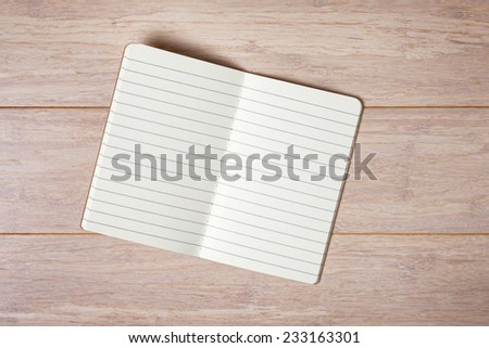 Top view of open note book on wooden background - stock photo