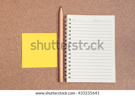 Top view of open spiral notebook, empty line paper with brown pencil and yellow sticky notes - notebook paper on brown background - stock photo