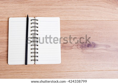 Top view of open spiral notepad and black pencil on wooden desktop. Mock up - stock photo