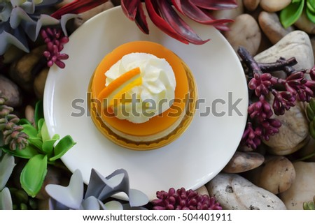top view of orange cake with orange topping and whipped cream in white dish on wooden top