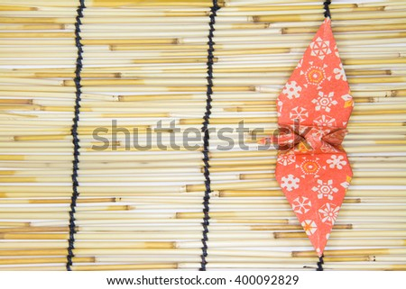 Top view of orange color traditional Japanese origami crane on bamboo wallpaper - stock photo