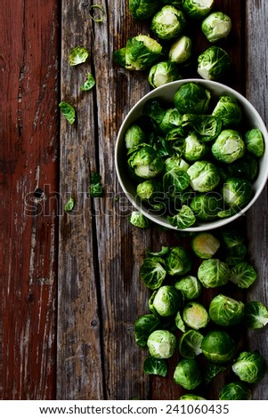 Top view of organic brussel sprouts in a white bowl on rustic wooden table.  - stock photo