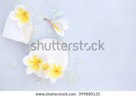 Top view of organic cream and soap bar with frangipani flower
