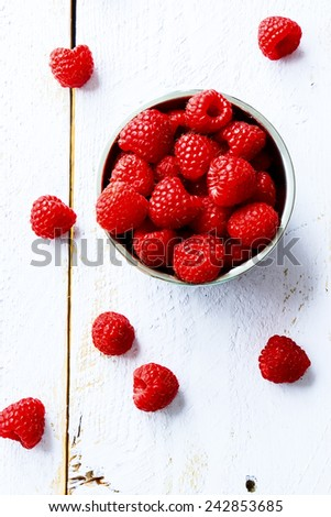 Top view of organic raspberry in bowl on white wooden board.  - stock photo