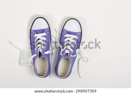 top view of pair of purple sneakers on white - stock photo