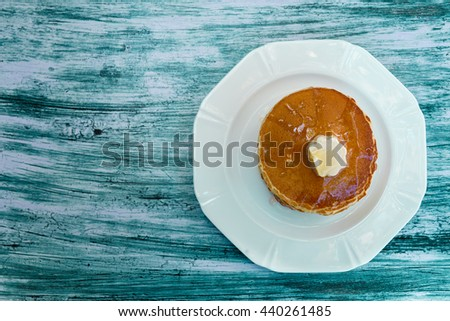 Top view of pancakes with butter and honey or maple syrup on white plate on blue wooden background. Copy space, frame - stock photo