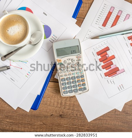 Top view of paperwork and graphs spread out with a calculator and cup of coffee on a wooden business desk. Accountancy concept. - stock photo