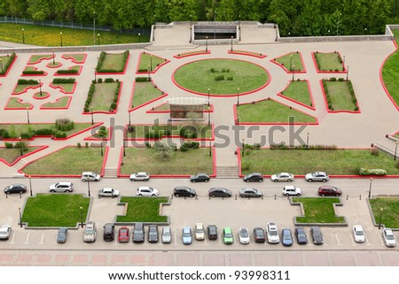 Top view of parking with parked cars; green grass and footpaths - stock photo