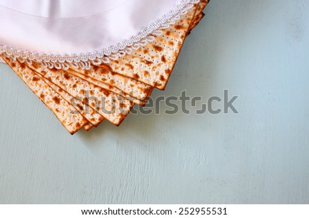 top view of passover background. matzoh (jewish passover bread) and traditional seder plate over wooden background - stock photo