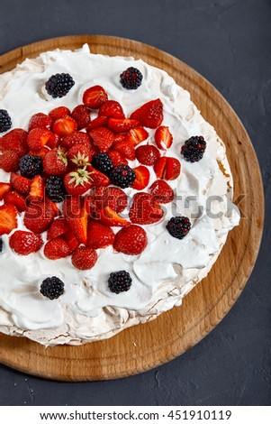 Top view of Pavlova cake with strawberry and blackberries. Two layers of french meringue and whiped cream with many berries. - stock photo
