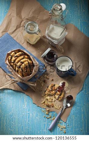 Top view of peanut biscuits, jars with jam and condensed milk, bottle with milk on the blue  crackled background - stock photo