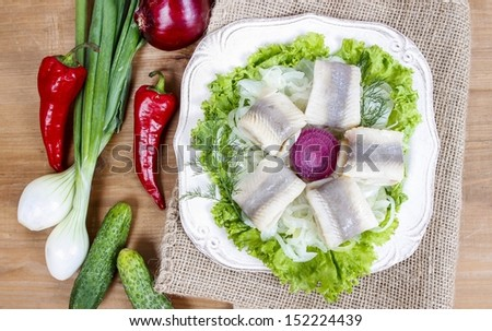 Top view of pickled herring with fresh vegetables on brown wooden table. - stock photo