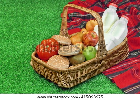 Top View Of Picnic Scene With Basket And Blanket On The Fresh Grass - stock photo