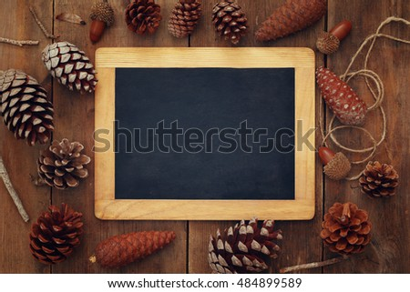 Top view of pine cones and blank blackboard on rustic wooden background