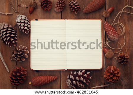 Top view of pine cones and blank open notebook on rustic wooden background. retro filtered