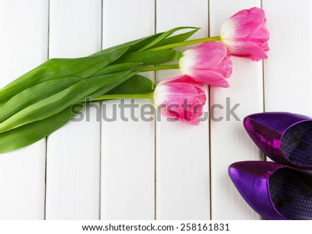Top view of pink tulips with purple women's shoes on white wooden background - stock photo