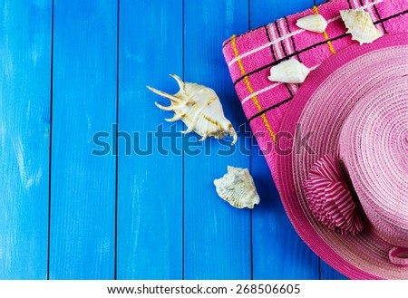 Top view of pink woven hat with towel and shells on blue wooden background with place for your text - stock photo