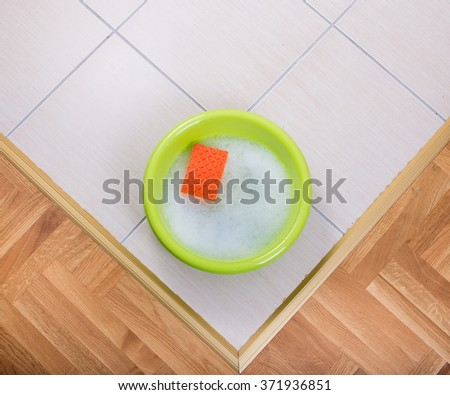 Top view of plastic washbasin with foam and sponge on tiled floor - stock photo