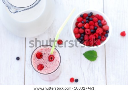 Top view of raspberry and blueberry milkshake on white wooden table - stock photo