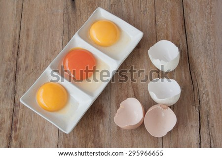 Top View of Raw Egg with Yellow Yolk and Broken Shell Halves  - stock photo