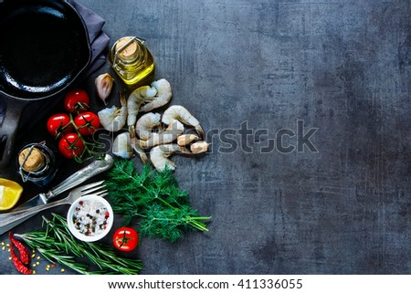 Top view of raw ingredients for preparing fresh seafood with shrimp, tomatoes, fresh herbs and spices on dark vintage background, place for text, border. - stock photo