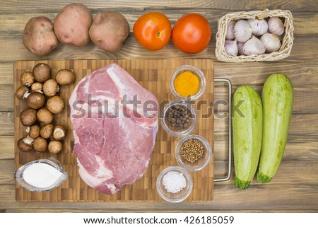Top view of Raw pork meat on a wooden table, ingredients for stew - vegetables, meat , spices. flat lay - stock photo