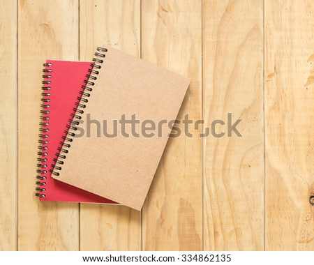 Top view of red and brown book on wooden table background - stock photo