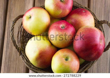 Top view of red apples in the basket on wooden background