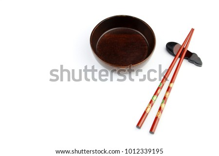 Top view of red chopsticks and Wood bowl on white table background.Flat lay