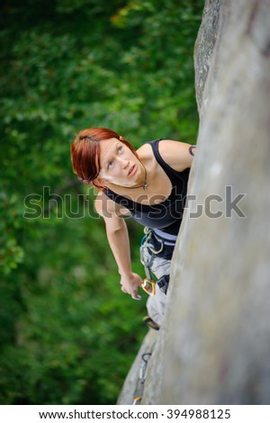 Top view of red-haired athletic female climbing steep cliff wall in summer time. Sport and Healthy lifestyle concept. - stock photo