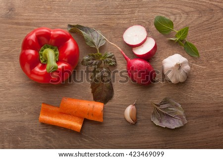 Top view of red paprika, sliced radish, two pieces of carrot, garlic and leaves of basil on the wooden table