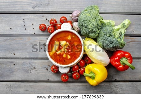 Top view of red tomato soup on wooden table. Fresh vegetables around. Symbol of healthy living - stock photo