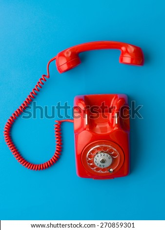 top view of red vintage phone with handset off the hook, on blue background - stock photo