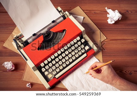 Top view of red vintage typewriter with white blank paper sheet with male hand holding pencil making drafts, on wooden table