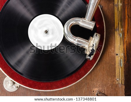 Top view of retro gramophone with vinyl spinning.Focus on the arm. - stock photo