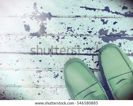 Top view of Retro green shoes on grunge blue wood abstract background with flare light and copy space.Concept hipster style and lifestyle texture.