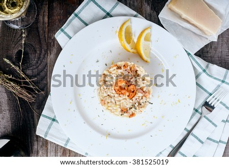 Top view of Risotto with shrimps and thyme in plate on wood background. Parmesan cheese near plate - stock photo