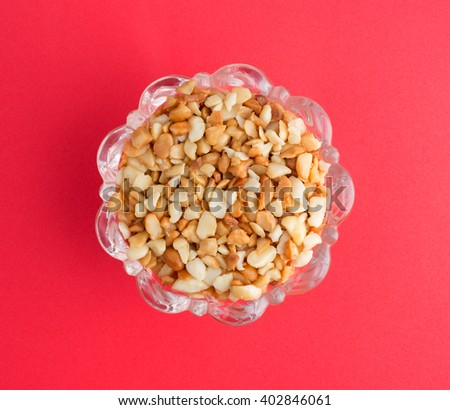 Top view of roasted and salted macadamia nut pieces in a glass bowl atop a bright red background. - stock photo