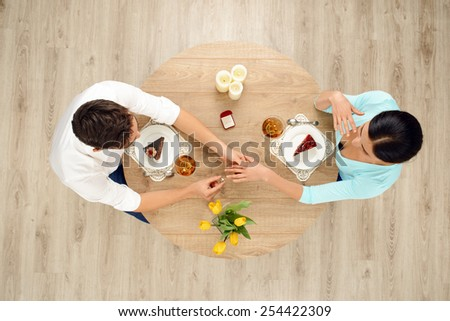 Top view of round table with couple on date. Man putting ring on the left hand of woman. Proposal of marriage concept - stock photo