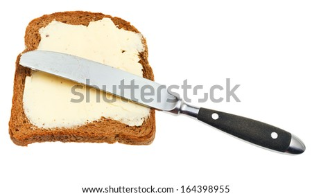 top view of rye bread and dairy butter sandwich and table knife isolated on white background - stock photo
