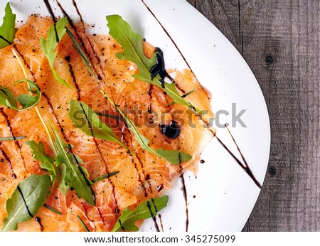 Top view of salmon carpaccio with arugula leaves and sticky balsamic vinegar on wooden background. - stock photo